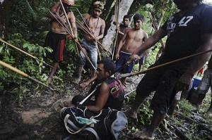 Munduruku Indian warriors stand guard over an illegal gold miner in western Para state